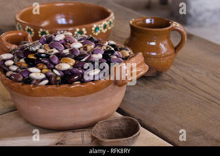 mexican hand made clay pot full with a wide variety of bean seeds, mexican clay mug, vintage rustic wood table and spoon - Stock Photo