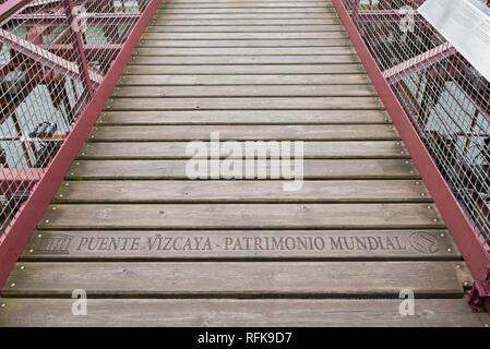 lettering (unesco puente vizcaya-patrimonio mundial) on the suspension bridge of bizkaia (puente de vizcaya) between getxo and portugalete above the r - Stock Photo