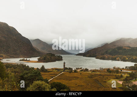 View onto Loch Shiel in Glenfinnan near the Glenfinnan Viaduct with Glenfinnan Monument and fog covered mountains during autumn (Scotland, Europe) - Stock Photo