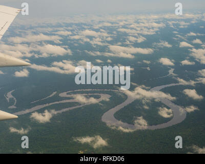 View from airplane window. Wing of an airplane flying above the clouds over Amazon River. Top View of Amazon rainforest. Peru, Brazil. Colombia. - Stock Photo