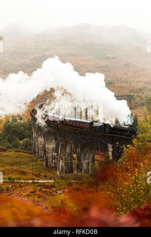 Steam train passing Glenfinnan Viaduct with fog covered mountains in the background during a moody autumn day (Glenfinnan, Scotland, Europe) - Stock Photo