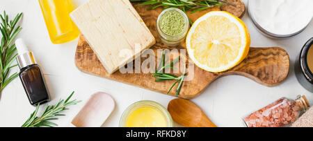 Spa still life with organic ingredients , top view of natural soap, clay, essential oil, rosemary herb, lemon and bath salt on wooden board, organic i - Stock Photo