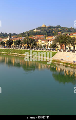 Adige River and distant hilltop Sanctuary our Lady of Lourdes from the Ponte Pietra, Verona, Veneto, Italy. - Stock Photo