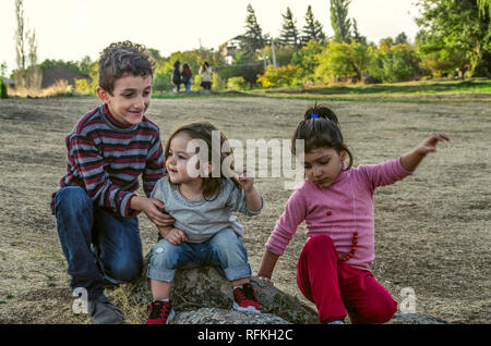 Ashtarak,Armenia,10 September,2018: Little boy and two little girls met and became friends in the courtyard of Saghmosavank Church in the autumn eveni - Stock Photo