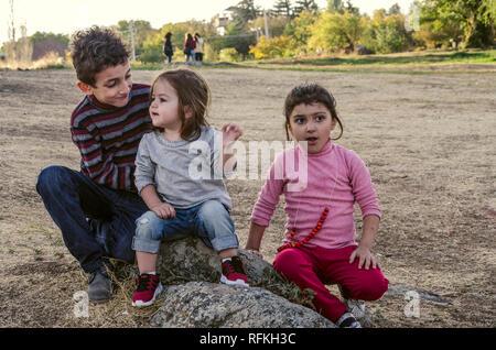 Ashtarak,Armenia,10 September,2018:In the courtyard of the Church Saghmosavank autumn evening, a friendly conversation between a little girl and a lit - Stock Photo