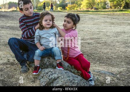 Ashtarak,Armenia,10 September,2018:In the courtyard of the Church Saghmosavank autumn evening, a little girl and a little boy correct hair from one ye - Stock Photo