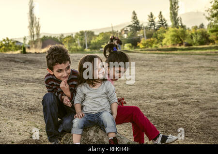 Ashtarak,Armenia,10 September,2018:Two little girls and little boy met and became friends in the courtyard of Saghmosavank Church in the autumn evenin - Stock Photo