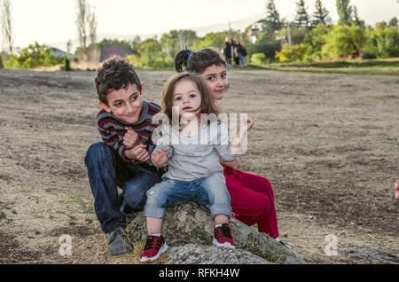 Ashtarak,Armenia,10 September,2018:In the courtyard of the Church Saghmosavank autumn evening one-year-old girl tells something to children,a little g - Stock Photo