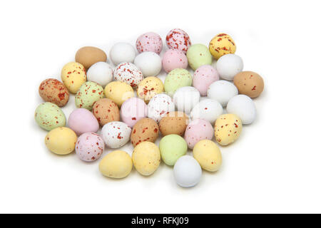 Selection of multi coloured pastel mini eggs representing Easter, on a white background. - Stock Photo
