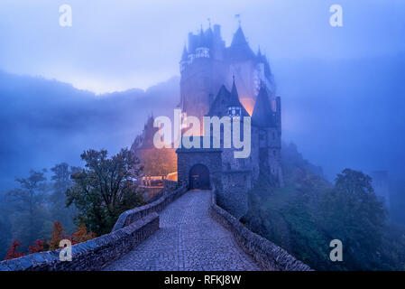 The medieval gothic Burg Eltz castle in the morning mist, Germany. Eltz Castle is one of the most impressive and famous castles in Germany. - Stock Photo