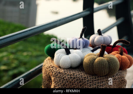 Group of colorful pumpkin ornament knit from yarn on outside table with green background, near banister, photo focus on autumn pumpkins with blurred b - Stock Photo