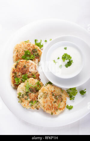 Cabbage pancakes with parsley and yogurt dressing on a white plate. Top view - Stock Photo