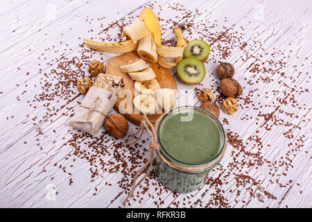 healthy green smoothie with walnut and fruits lie on the table - Stock Photo