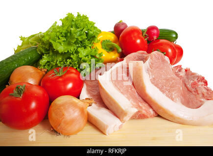 Raw pork and vegetables. Isolated over white - Stock Photo