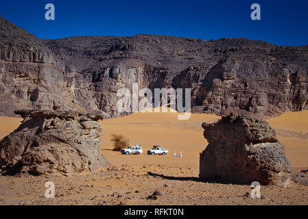 TASSILI N'AJJER, ALGERIA - JANUARY 10, 2002: unknown men with their off-road vehicles in the sand dunes of the Algerian Sahara desert, Africa, Tassili - Stock Photo