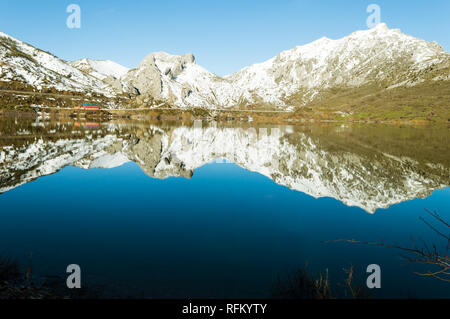 The hills covered with snow are reflected in a lake of Barrios De Luna, Leon, Spain, on a beautiful winter evening - Stock Photo