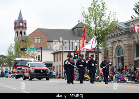 Stoughton, Wisconsin, USA - May 20, 2018: Annual Norwegian Parade, Firefighters in uniform, carrying axes and flags, marching down the road during the - Stock Photo