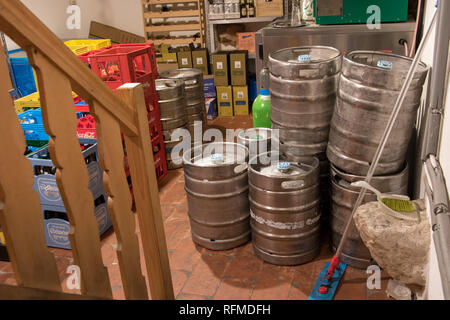 The depot of pub with barrels of beer. Beverage storage in the basement cellar. Storage of casks with beer and crates with bottles for restaurant. - Stock Photo