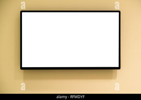 Modern blank high definition LCD flat screen TV monitor, isolated on yellow wall background - Stock Photo