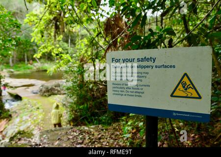 For your safety take care on slippery surfaces sign, Granite bend track to broken river, Eungella National Park, Queensland, Australia - Stock Photo