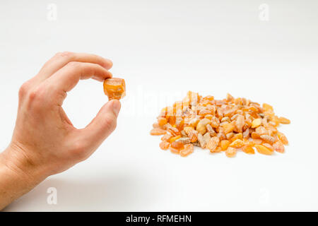 Mans hand holding an amber stones from Baltic sea on clean white background - Stock Photo