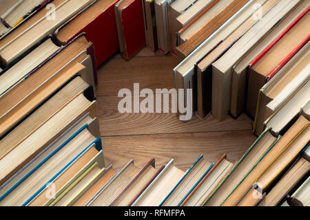 Love concept of heart shape from old vintage books on wooden floor background. Vintage colour tone style composition of love with open book heart - Stock Photo
