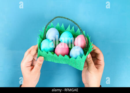 DIY basket Easter egg from cardboard tray, crepe paper, chenille stem on blue background. Gift idea, decor spring, Easter. Handmade. Step by step. Pro - Stock Photo