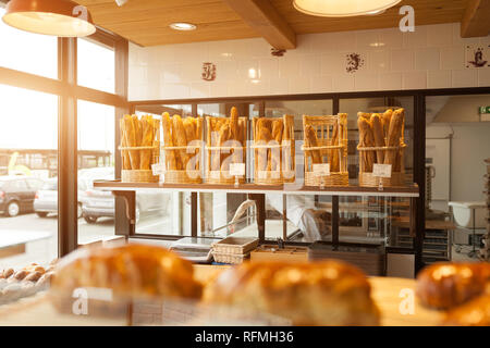 Brest, France 28 May 2018 Modern bakery with different kinds of bread, cakes and buns with sunlight on the background - Stock Photo
