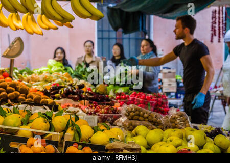 Market trader is selling fruits and vegetables at Rialto Market, Mercato di Rialto to tourists - Stock Photo