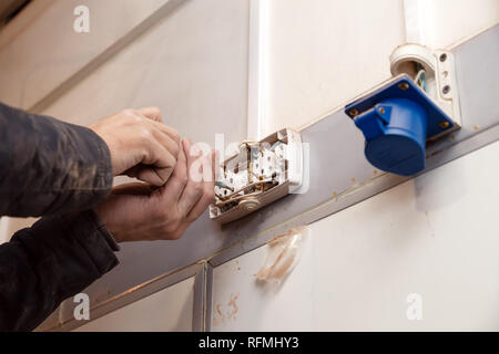 Closeup of man electrician's hand repairing an electrical outlet, socket in the wall. Hazardous concept, high voltage, risk, wiring replacement - Stock Photo