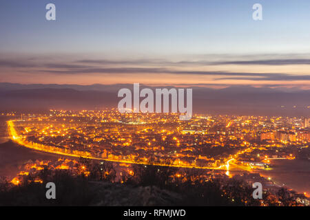 Stunning late blue hour view of Pirot cityscape with hot city lights and colorful sky - Stock Photo