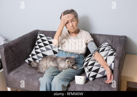 The topic is very old person and health problems. A senior Caucasian woman, 90 years old, with wrinkles and gray hair, sits home on sofa with pet cat  - Stock Photo