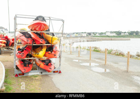 In sunlight, red, yellow and white kayaks placed upside down on metal storage racks. Stocked canoe in the Brest, France 28 May 2018. - Stock Photo