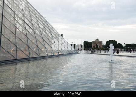 PARIS, FRANCE. 01 June 2018: Louvre Museum square during a summer sunset. The old renaissance building is enlightened by the sun and the glass pyramid - Stock Photo