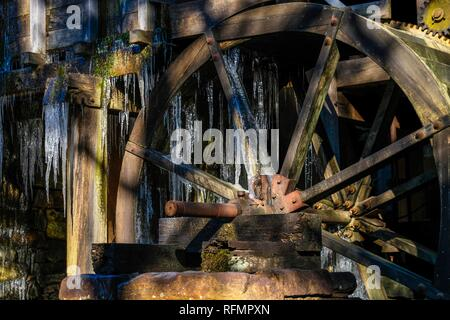 Long icicles hang from the waterwheel of the old gristmill on a cold winter morning at Historic Yates Mill County Park in Raleigh North Carolina. - Stock Photo