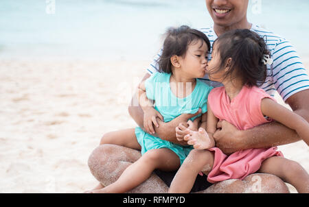 two little girls kissing each other when on dad's lap - Stock Photo