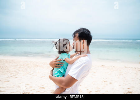 father and his daughter kissing each other on the beach  - Stock Photo