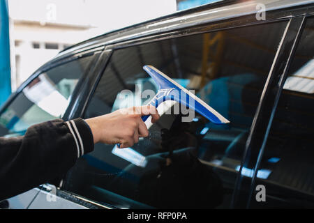 Car wash and detailing - the man holds the microfiber in hand and polishes or washing the car. Man cleaning automobile with sponge at car wash - Stock Photo