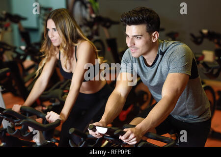 Two people biking in the gym, exercising legs doing cardio workout cycling bikes. Couple in a spinning class wearing sportswear. - Stock Photo