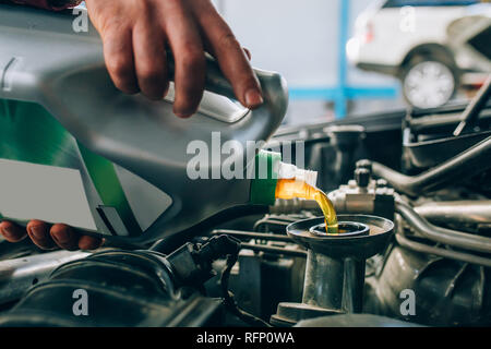 Auto mechanic working in garage during the maintenance of engine. Mechanician holding wrench tool, during Repair of a car in auto service garage - Stock Photo