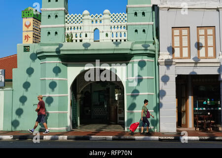 People passing Jamae Mosque in Chinatown, Singapore, the shadows of Chinese lanterns hanging over the street seen on the mosque wall - Stock Photo