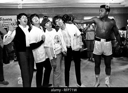 FILE - In this Feb. 18, 1964, file photo, The Beatles, from left, Paul McCartney, John Lennon, Ringo Starr, and George Harrison, take a fake blow from Cassius Clay, who later changed his name to Muhammad Ali,  while visiting the heavyweight contender at his training camp in Miami Beach, Fla. Ali turns 70 on Jan. 17, 2012. (AP Photo/File) - Stock Photo