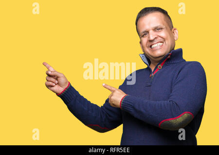 Middle age arab man over isolated background smiling and looking at the camera pointing with two hands and fingers to the side. - Stock Photo
