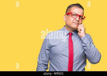 Middle age arab man wearing fashion red glasses over isolated background with hand on chin thinking about question, pensive expression. Smiling with t - Stock Photo