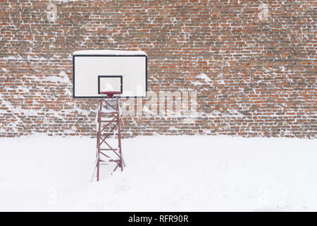 Basketball hoop in the winter, covered with snow. - Stock Photo