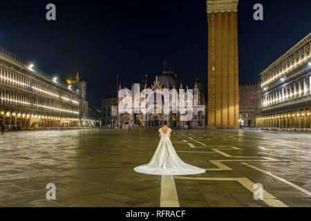 A bride in a wedding dress is standing on San Marco Square, Piazza San Marco, at night - Stock Photo
