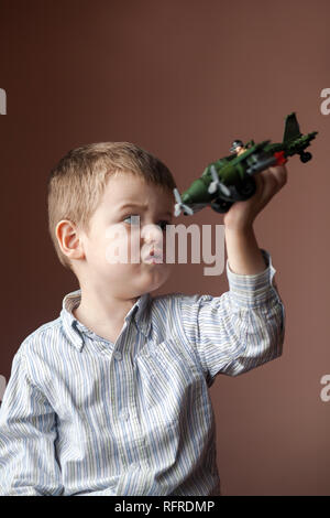 Cute little boy playing with a toy airplane. Military Aircraft LEGO - Stock Photo