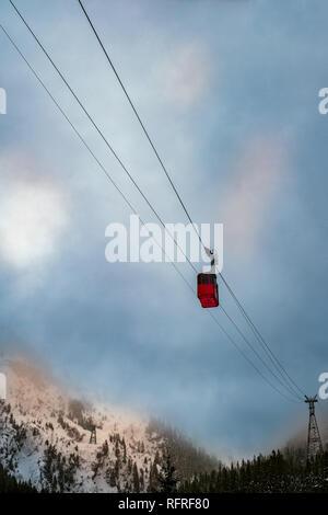 red cable car with dramatic sky in Fagaras Mountains, Balea lake, Sibiu county,  Transylvania, Romania, Europe - Stock Photo