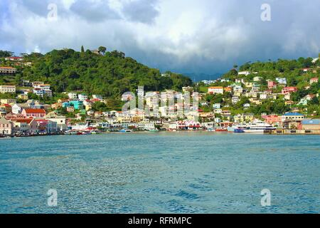 St George's, Grenada, Caribbean - February 23rd 2018: The colorful buildings of Grenada brighten the landscape despite the cloudy weather. - Stock Photo