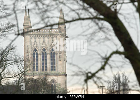 Trio of cloned windows on the upper part of the tower at St John's college, University of Cambridge, England, as seen from trees on a winter's day. - Stock Photo